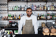 Portrait of smiling male owner standing at checkout counter in restaurant - MASF07459