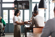 Customer giving credit card to young waiter at restaurant - MASF07474
