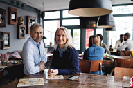 Portrait of smiling mature couple with menu at wooden table against people in restaurant - MASF07492