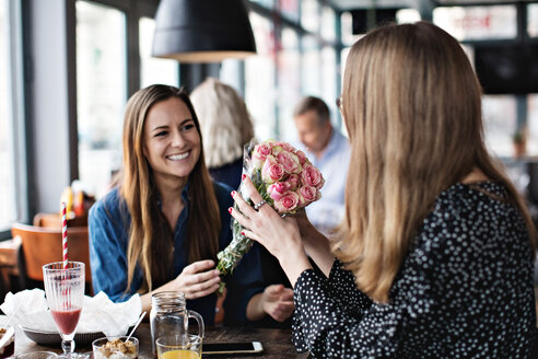 Smiling young woman giving fresh flower bouquet to female friend sitting at restaurant - MASF07522