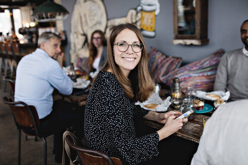 Portrait of smiling woman holding mobile phone while sitting with friends at table - MASF07549