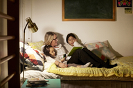 Grandmother reading book to granddaughters while sitting on bed at home - MASF07582