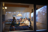 Happy family having dinner at table seen through glass window during sunset - MASF07585