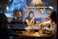 Multi-generation family enjoying dinner at table seen through glass window - MASF07588