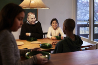 Happy family talking while sitting at illuminated table - MASF07600