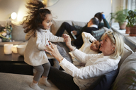Girl playing with grandmother on sofa by family at home - MASF07603