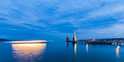 Germany, Constance, view to port entrance with lighthouse and Imperia at twilight - WDF04644