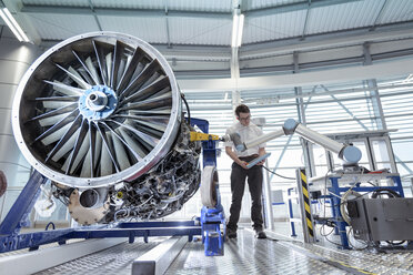 Engineer using robotic metrology to measure jet engine in robotics research facility - CUF00025