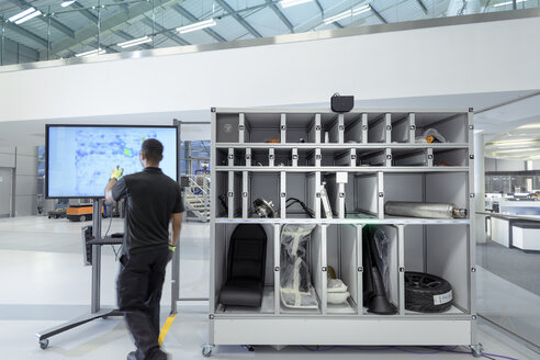Engineer using artificial intelligence aid to pick parts for product assembly in robotics research facility - CUF00043