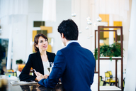 Businessman and businesswoman having drink at bar - CUF00076