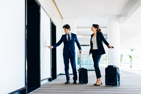 Businessman and businesswoman with wheeled luggage waiting for hotel escalators - CUF00085