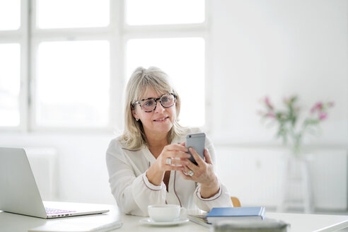 Mature businesswoman looking at cell phone at desk - HHLMF00248