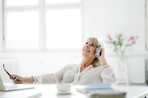 Happy mature businesswoman on cell phone at desk - HHLMF00251