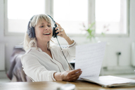 Laughing mature businesswoman wearing headphones looking at document at desk - HHLMF00254