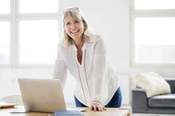 Portrait of happy mature businesswoman with laptop leaning on desk - HHLMF00257
