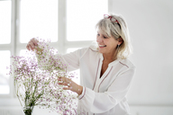 Smiling mature woman caring for flowers - HHLMF00260