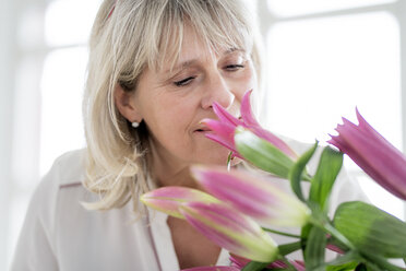 Mature woman smelling at bunch of flowers - HHLMF00263