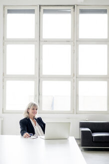 Smiling mature businesswoman working on laptop at desk in the office - HHLMF00266