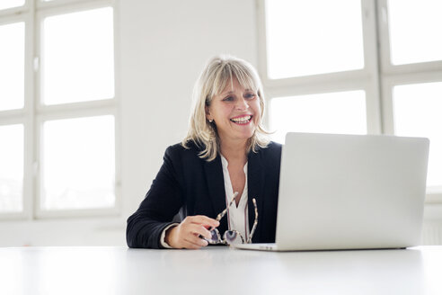 Smiling mature businesswoman working on laptop at desk in the office - HHLMF00269