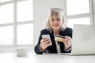 Mature businesswoman with smartphone, credit card and laptop at desk in the office - HHLMF00272