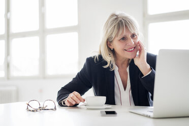 Smiling mature businesswoman with cup of coffee working on laptop at desk in the office - HHLMF00275