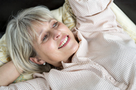 Happy mature woman lying down relaxing - HHLMF00284