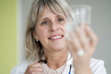 Smiling mature woman holding glass of water - HHLMF00290