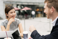 Young businesswoman and man having discussion at sidewalk cafe - ISF00003