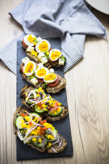 Vegetarian breakfast with bread, eggs and tomato slices and cucumber slices on slate - GIOF03937