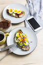 Vegetarian breakfast with bread, eggs and cucumber slices on plate, smartphone, latte macchiato, coffee cup - GIOF03943