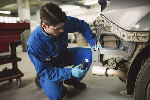 Mechanic inspecting a car with a torch in a workshop - RAEF01992