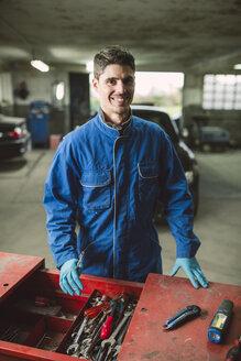 Portrait of smiling mechanic in his workshop - RAEF01995