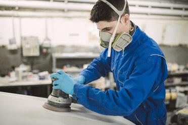 Man polishing the hood of a car in a workshop - RAEF01998
