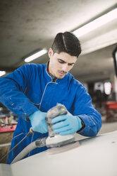 Man polishing the hood of a car in a workshop - RAEF02001