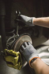 Close-up of mechanic fixing the brake caliper of a car in a workshop - RAEF02004