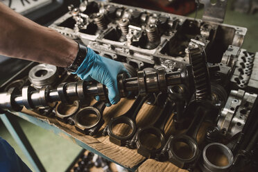 Close-up of mechanic holding the crankshaft of the engine of a car in a workshop - RAEF02013