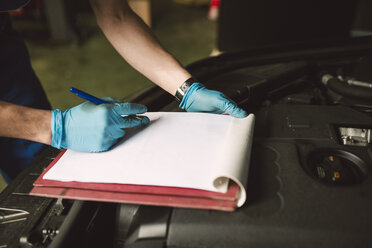 Close-up of mechanic taking notes on clipboard in his workshop - RAEF02019