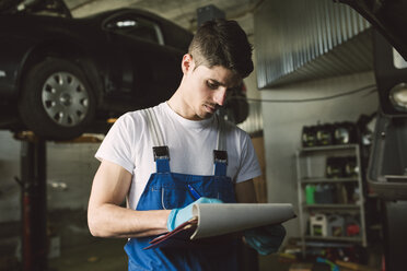 Mechanic with clipboard and checklist in his workshop - RAEF02022