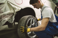 Mechanic changing car tyre in his workshop - RAEF02025