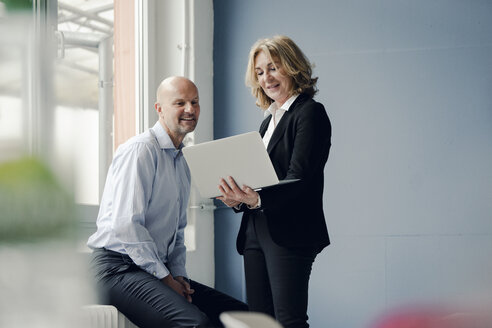 Businessman and businesswoman working together on laptop - KNSF03801