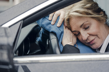 Senior businesswoman sleeping in car - KNSF03816