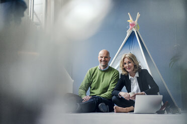 Smiling businessman and businesswoman sitting at teepee indoors with laptop - KNSF03819