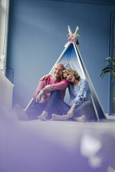 Smiling couple sitting at teepee indoors - KNSF03828
