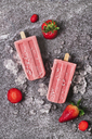 Two homemade strawberry ice lollies, ice and strawberries on marble - RTBF01252