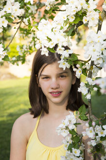Portrait of girl with twig of blossoming apple tree - LVF06925