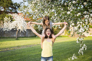 Girl carrying little sister on her shoulders in the garden - LVF06931