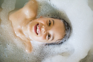 Portrait of happy little girl bathing in a tub - LVF06934