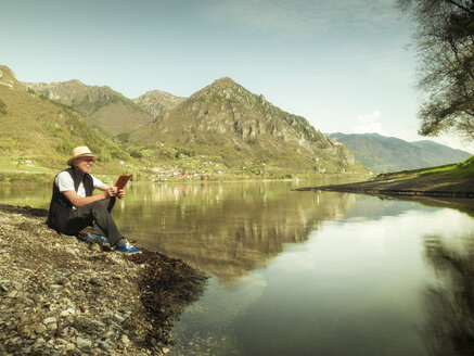 Italy, Anfo, senior man sitting at Lake Idro using tablet - LAF02014