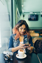 Smiling woman sitting in coffee shop looking at cell phone - JPF00312