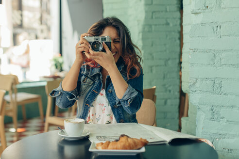 Laughing woman sitting in coffee shop taking pictures with camera - JPF00315